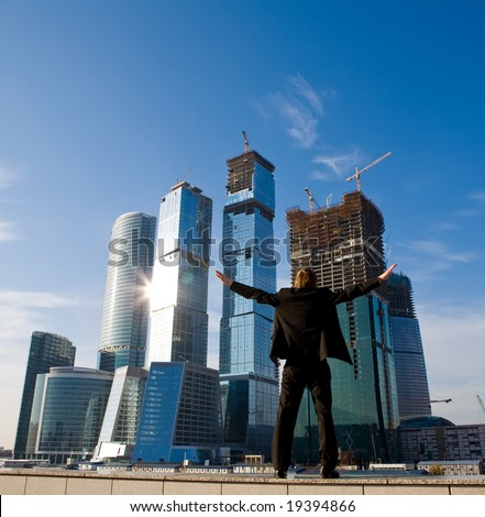 Businessman standing with outstretched arms against skyscraper in Moscow City - stock photo