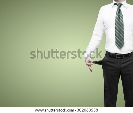businessman standing with pockets turned inside out on gray background - stock photo