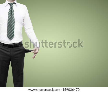 businessman standing with pockets turned inside out on green background - stock photo