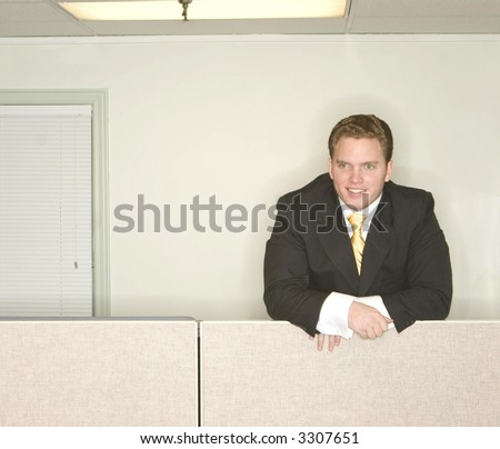 Businessman stands and looks ahead with a smile on his face while standing above his office cubicle