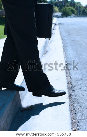 Businessman steps down from sidewalk onto the street