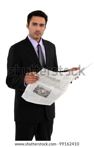 Businessman stood reading the daily newspaper - stock photo
