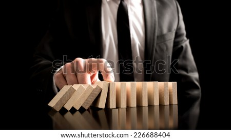 Businessman Stopping the Domino Effect from Small Wooden Blocks on the Table. A Creative Concept for Solution to Problem. - stock photo