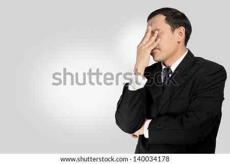 Businessman stressed on gray background.