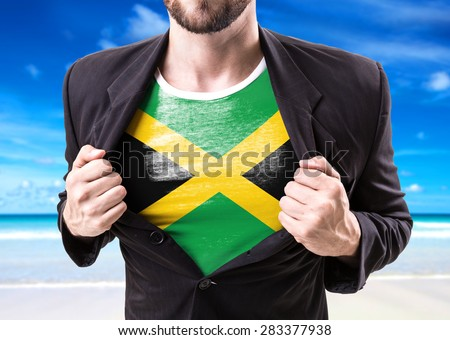 Businessman stretching suit with Jamaica Flag on beach background - stock photo