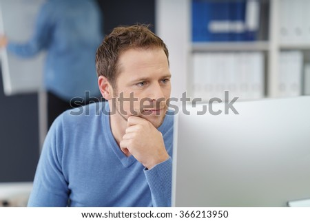 Businessman studying his desktop monitor with a serious look of concentration as he rests his chin on his hand, close up view