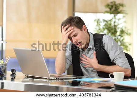 Businessman suffering an anxiety attack with the hands in his chest and head sitting in a desktop at office - stock photo