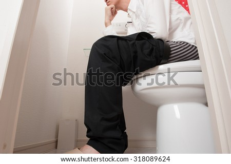 Businessman suffering in the toilet