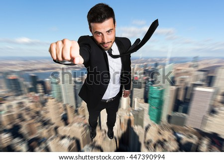 Businessman superhero flying over a city