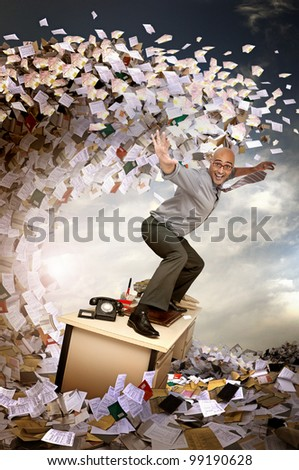 Businessman surfing in a sea of papers and files - stock photo