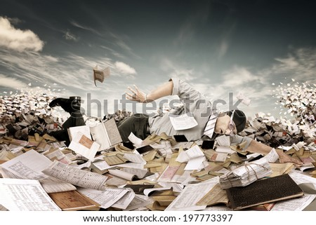 Businessman swimming in a sea of papers