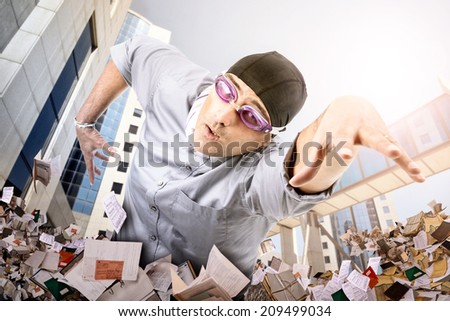 Businessman swimming in a sea of papers - stock photo