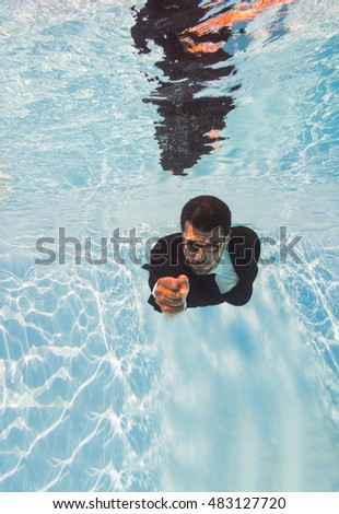 businessman swimming underwater in the pool