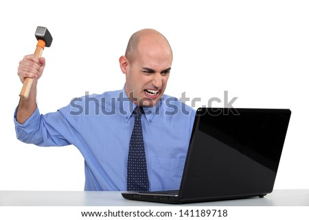 Businessman taking a hammer to his laptop - stock photo