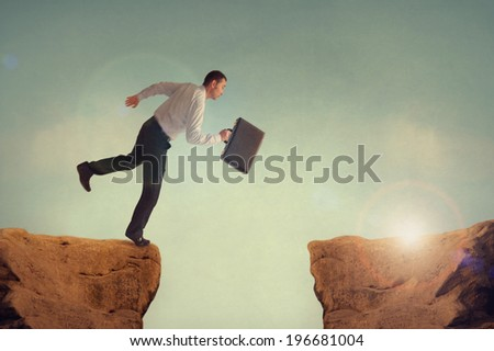 businessman taking a risk leaping to meet the challenge - stock photo