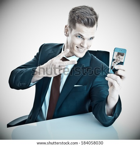 Businessman taking a selfie - stock photo