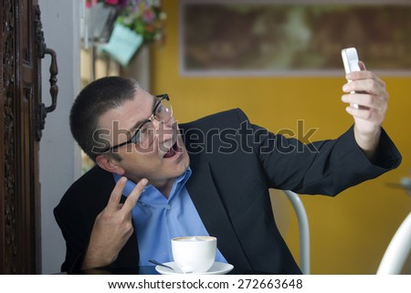 Businessman taking a selfie at cafe - stock photo