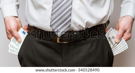 Businessman taking dollars  and euro out of pockets, closeup shot - stock photo