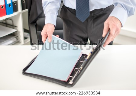 Businessman taking folder from his briefcase at office