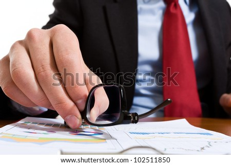 Businessman taking his eyeglasses from the desk - stock photo