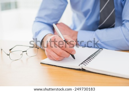 Businessman taking notes on notebook in his office