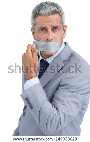 Businessman taking off duct tape on mouth on white background - stock photo