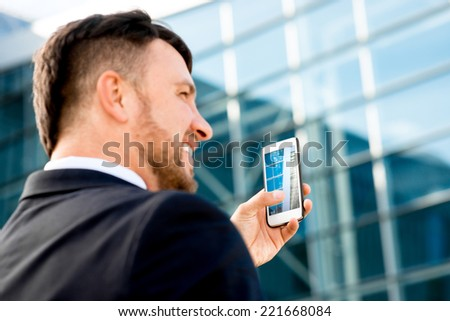 Businessman taking photo of contemporary building with cellphone