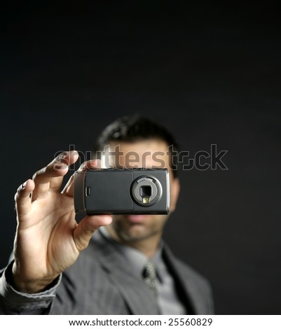 Businessman taking photos, mobile camera, black background