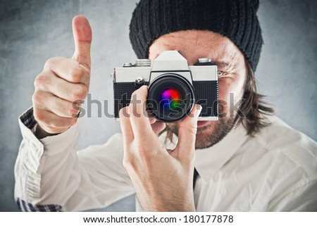Businessman taking picture with old vintage film photo camera