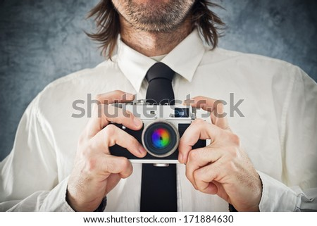 Businessman taking picture with retro style photo camera - stock photo