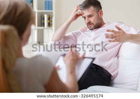 Businessman talking about his job on psychotherapy session - stock photo