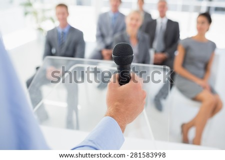 Businessman talking in microphone during conference in meeting room