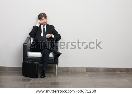 Businessman talking on a mobile and looking at your watch. - stock photo