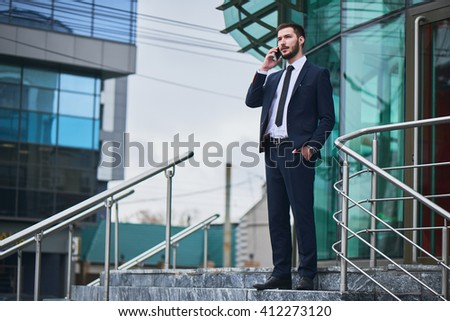 Businessman talking on cell phone standing on a ladder against the building with a glass facade