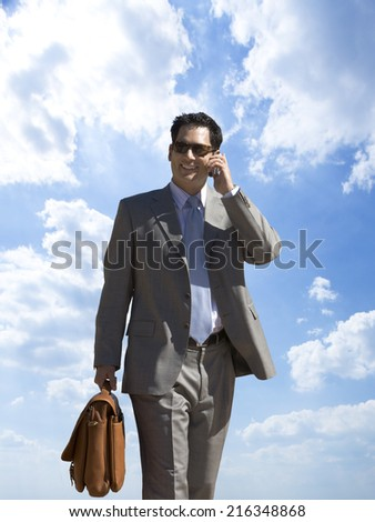 Businessman talking on cell phone with background of clouds in blue sky