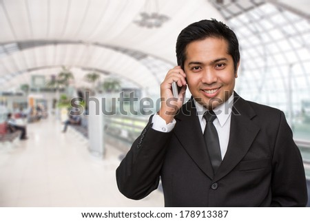 Businessman talking on cellphone at airport