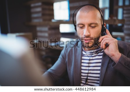 Businessman talking on headphones while sitting in creative office