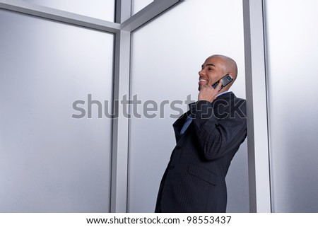 Businessman talking on his cell phone and smiling, beside an office window.