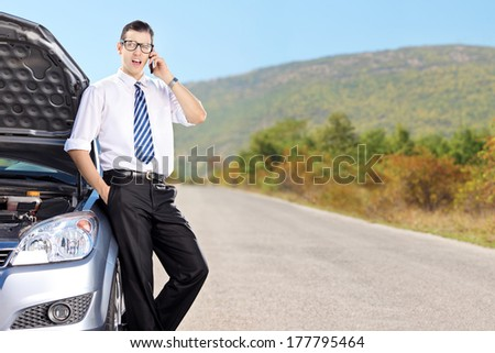 Businessman talking on mobile phone and resting on a car with its bonnet open. - stock photo