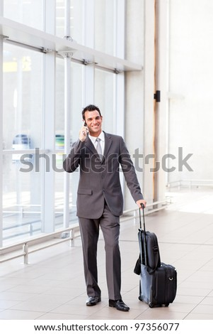 businessman talking on mobile phone at airport