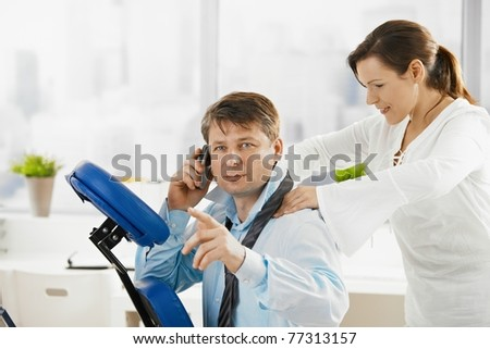 Businessman talking on mobile while getting neck massage in office.? - stock photo