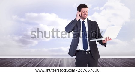 Businessman talking on phone holding laptop against clouds in a room - stock photo