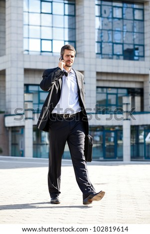 businessman talking on phone while walking outdoors of a modern office building