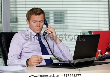 Businessman talking on telephone and looking at card in office