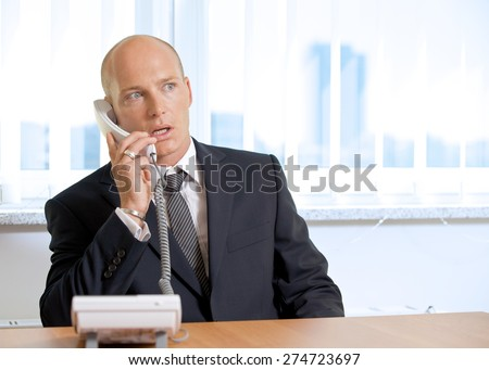 Businessman talking on telephone at office