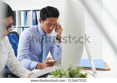 Businessman talking on telephone when working in office