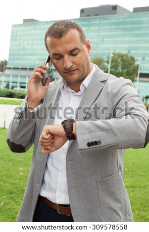 Businessman talking on the phone and looking at his watch - stock photo