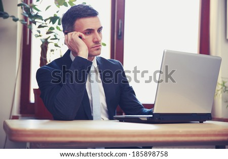 Businessman talking on the phone and using laptop in office - stock photo