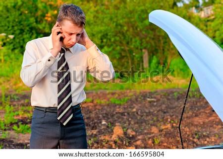 businessman talking on the phone near the broken car - stock photo
