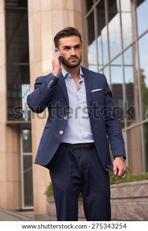 Businessman talking on the phone walking on the street - stock photo